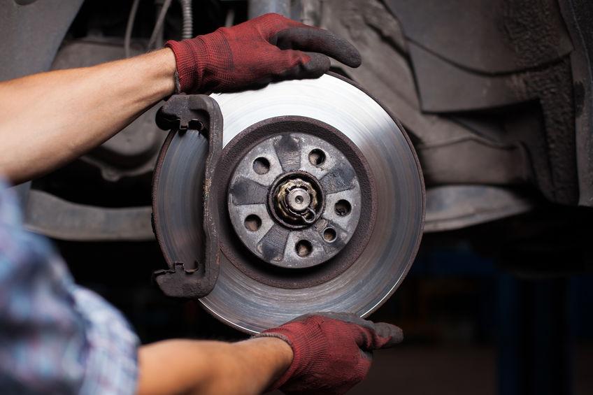 mechanic working on car brakes
